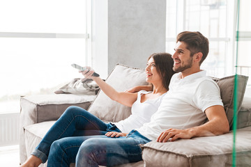 Couple sitting and watching TV at home