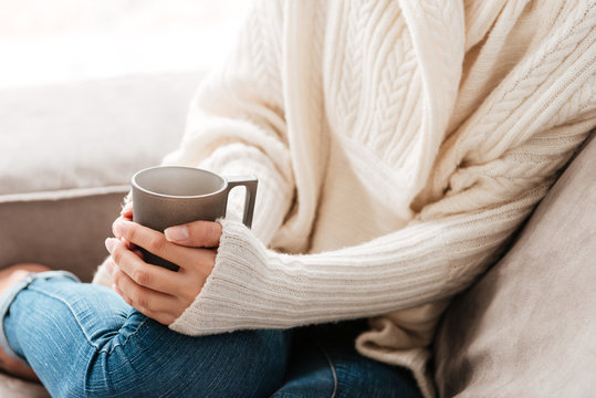 Woman with cup of coffee sitting on sofa at home