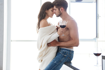 Beautiful sensual young couple embracing and drinking red wine