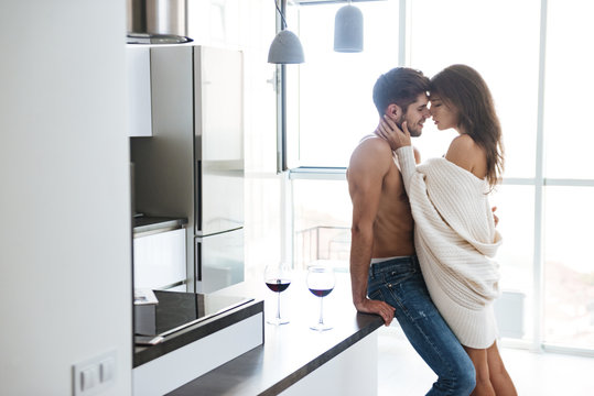 Sexy couple standing and hugging on the kitchen