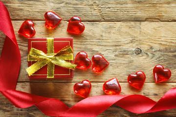red gift box, scarlet silk ribbon, transparent hearts