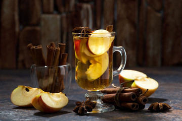 hot apple tea with spices on dark background