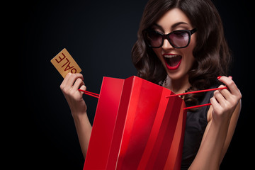 Happy woman open red bag on dark background in black friday holiday