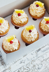 Vanilla cupcakes with a cap of cream on white wooden tablein the box