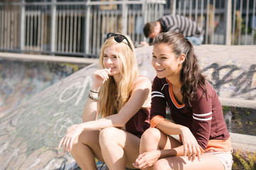 Two female skateboarders sitting in skatepark
