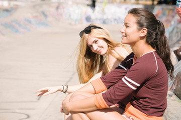 Two female skateboarders sitting in skatepark