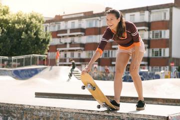 Female skateboarder preparing on skateboard ramp