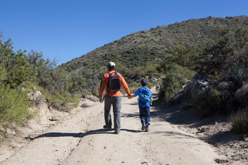 Rear view of man and son hiking dirt track in Andes, Valparaiso, Chile