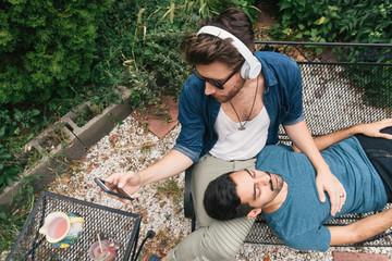 Homosexual couple relaxing in garden
