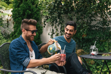Young male couple sitting in garden pouring cocktails