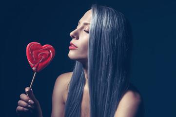 Frau mit Lutscher in Herzform