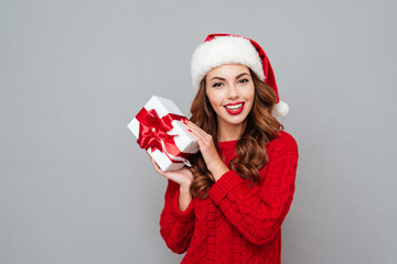 Happy young woman in santa claus hat holding gift box