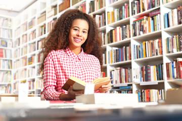 Czytanie książki. Młoda kobieta czyta ciekawą książkę w bibliotece