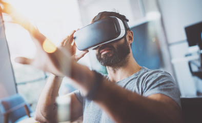 Closeup of bearded young man wearing virtual reality goggles in modern coworking studio. Smartphone using with VR headset. Horizontal, blurred.