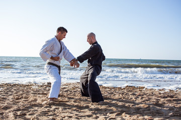 professional karate fighters training on the beach sea background