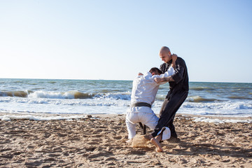 two professional karate fighters on the beach sea background