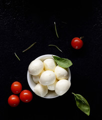 Top view of mozzarella cheese with cherry tomatoes and basil on a black slate surface