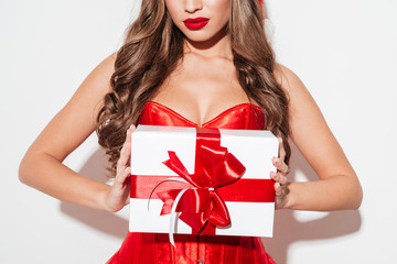 Sexy brunette woman in red dress holding big gift box