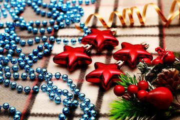 Unusual Christmas ornaments beautifully decorated, lying on warm plaid.