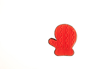 Red glove shaped gingerbread cookie. Isolated Christmas decoration on a white background. Copy space