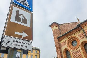 close up on road sign to Milan's Saint Mary church , Santa Maria Delle Grazie, hosting The Last Supper mural painting by Leonardo da Vinci. left side street view.