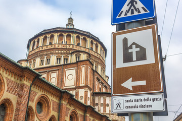 road sign close up to Milan's famous church Santa Maria Delle Grazie, hosting in it's refectory, The Last Supper mural painting by Leonardo da Vinci. street side view.