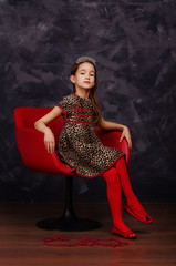 Pretty little girl wearing beautiful dress sitting in red armchair. She is wearing red masquerade carnival mask. Studio shot.