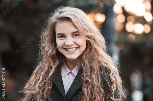 Smiling blonde teen girl 13-13 year old with curly hair wearing ...