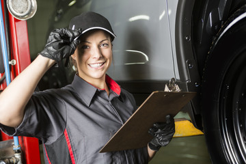 Mechanic woman working on car in his shop