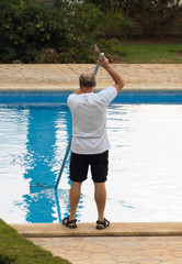 Man cleaning swimming pool with pole.