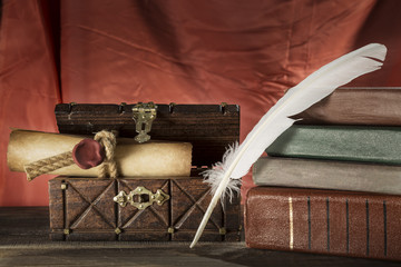 Vintage still life. Feather near sealed scroll in old chest and vintage books on red background