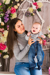 Young mother holding her newborn child. Woman and baby boy relax in a white bedroom. Nursery interior. Family at home