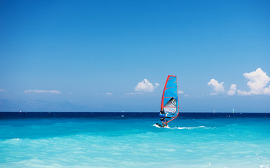 Windsurfing. Lonely surfer exercising on blue water.