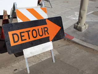 Orange on black detour arrow at street repair. Horizontal.
