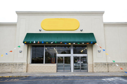 Storefront grand opening with blank yellow sign and banner flags. Horizontal.