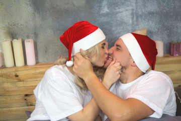Christmas. New Year. Man and woman in Christmas hats lie in bed, they smile it fun. Close-up