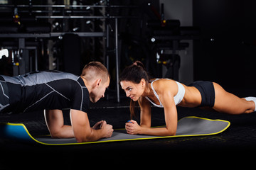 Woman doing abdominal crunches press exercise on the mat with her sports male trainer.