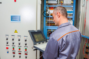 electrician testing industrial machine, electrician builder engineer screwing equipment in fuse box, Male Electrician,energy conservation, electrical work, repair of electricity power station,electric