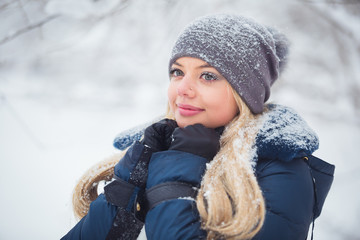 Cute young woman portrait playing with snow in warm woolen hat and coat in winter park