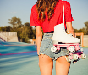Girl with long dark hair is back with white roller skates on her shoulder. Warm summer evening in the skate park. Outdoor. Close up.
