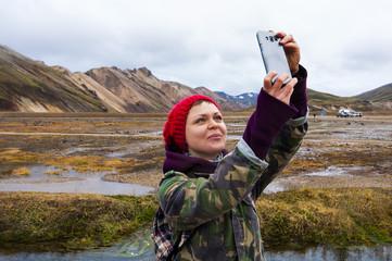 Iceland tourist young woman taking selfie photo with smartphone camera at landmark destination:Landmannalaugar.  Beautiful Icelandic Nature.
