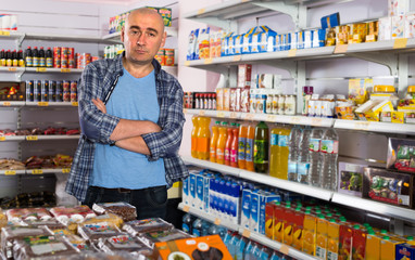 man near shelf with beverages in grocery.