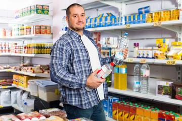 man choosing mineral water in grocery.