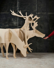 New Year's and Christmas decoration deer made of plywood and wood on a dark background