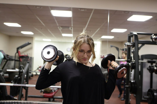 Teenager training with dumbbells
