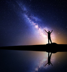 Milky Way. Night sky with stars and silhouette of a standing happy man with raised up arms on the mountain near the lake with reflection in water. Milky way and man on the hill. Galaxy. Universe