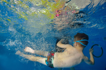 A child's spinning underwater in the pool in bubbles. Landscape orientation