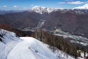 Ski slope in Sochi Krasnaya Polyana mountain resort at sunny day against snowy peak and blue sky winter background