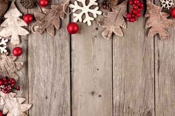 Rustic Christmas corner border with wood ornaments and berries on an aged wood background