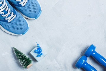 Christmas sport composition with shoes, dumbbells and blue gift